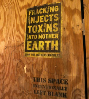 Photo of board with printing: Fracking injects toxins into Mother Earth