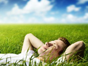 picture of a fellow sleeping on grass under a blue sky with clouds
